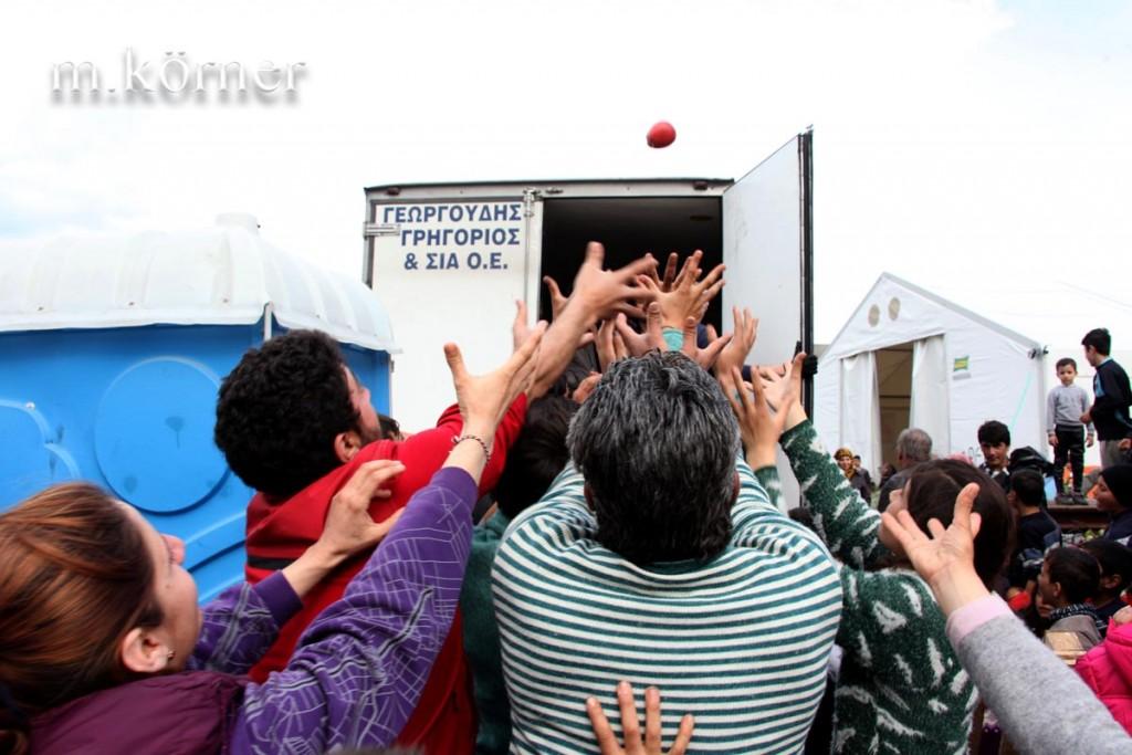 Flüchtlingslager in idomeni, griechenland 2016 / Menschen versuchen einen Apfel zu fangen. Eine Privatperson hatte eine Nahrungsspende unter den Flüchtlingen verteilt.